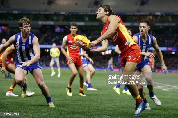 Lachie Weller of the Suns handpasses the ball during the round 16 AFL match between the North Melbourne Kangaroos and the Gold Coast Titans at Etihad...
