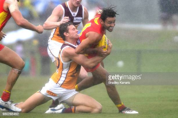 Lachie Weller of the Suns is pressured by the defence during the JLT Community Series AFL match between the Gold Coast Suns and the Brisbane Lions at...