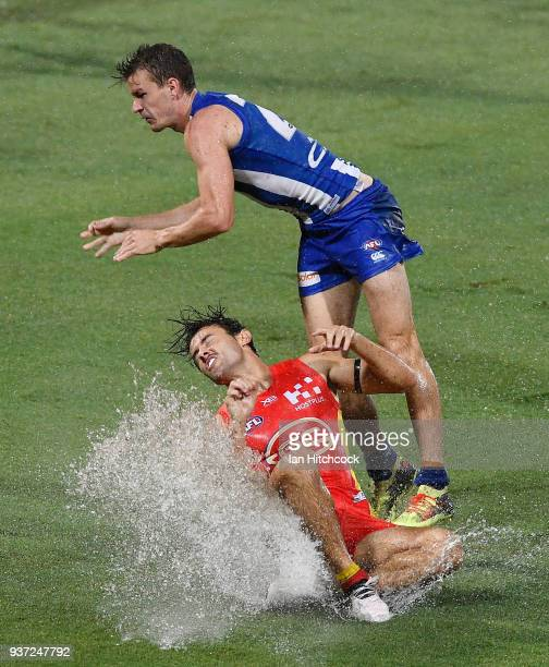 Lachie Weller of the Suns is tackled by Kayne Turner of the Kangaroos during the round one AFL match between the Gold Coast Suns and the North...