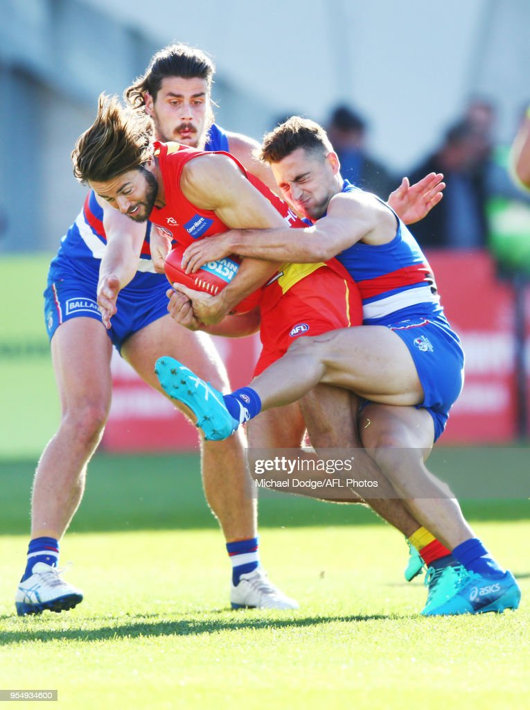 Lachie Weller of the Suns (C) is tackles by Tom Boyd (L) and Luke Dahlhaus of the Bulldogs during the round seven AFL match between the Western Bulldogs and the Gold Coast Suns at Mars Stadium on May 5, 2018 in Melbourne, Australia.