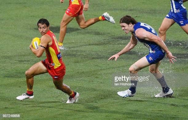 Lachie Weller of the Suns looks to get away from Ben Brown of the Kangaroos during the round one AFL match between the Gold Coast Suns and the North...