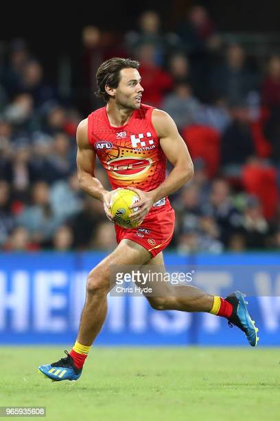 Lachie Weller of the Suns runs the ball during the round 11 AFL match between the Gold Coast Suns and the Geelong Cats at Metricon Stadium on June 2...