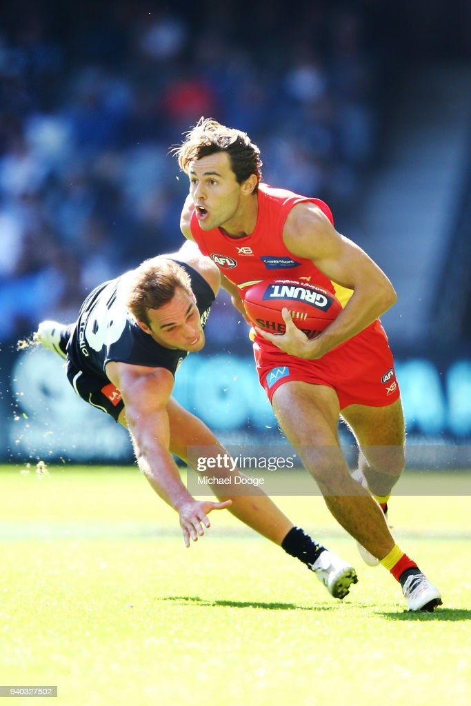 Lachie Weller of the Suns runs with the ball past David Cuningham of the Blues during the round two AFL match between the Carlton Blues and the Gold Coast Suns at Etihad Stadium on March 31, 2018 in Melbourne, Australia.
