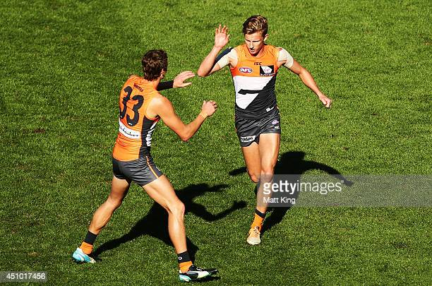 Lachie Whitfield of the Giants celebrates with Will HoskinElliott after kicking a goal during the round 14 AFL match between the Greater Western...