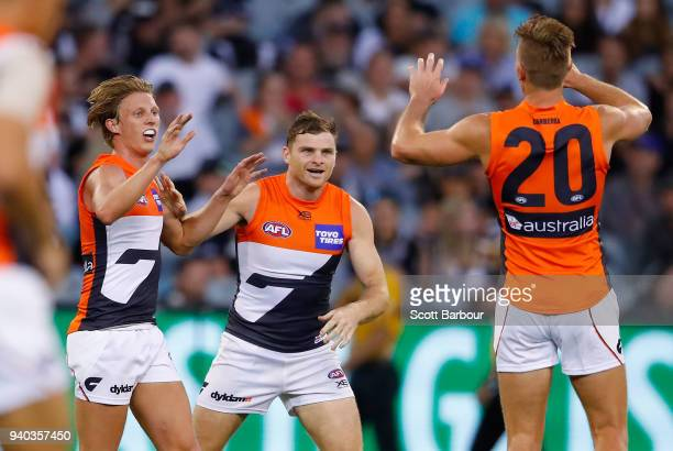 Lachie Whitfield of the Giants is congratulated by Heath Shaw of the Giants after kicking a goal during the round two AFL match between the...