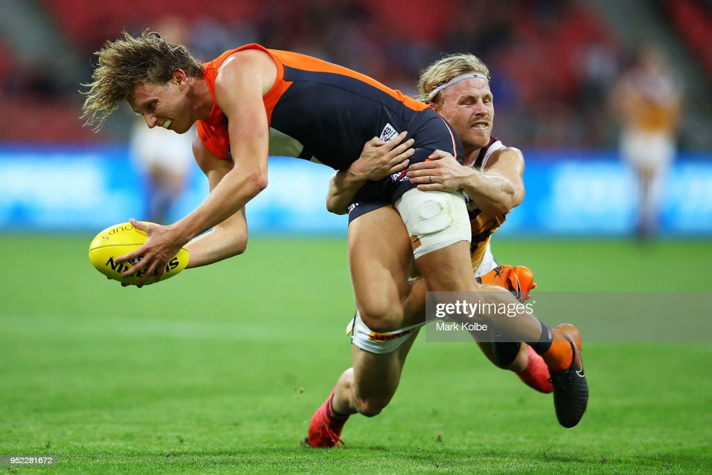 Lachie Whitfield of the Giants is tackled Daniel Rich of the Lions during the round six AFL match between the Greater Western Sydney Giants and the Brisbane Lions at Spotless Stadium on April 28, 2018 in Sydney, Australia.