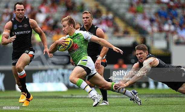Lachlan Croker of the Raiders beats the tackle of Christopher Lawrence of Wests Tigers during the match between the Wests Tigers and the Canberra...