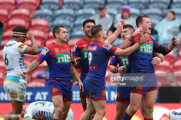 Lachlan Fitzgibbon of the Newcastle Knights celebrates a try with team mates during the round 24 NRL match between the Newcastle Knights and the Gold...