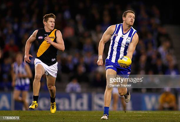 Lachlan Hansen of the Kangaroos handballs during the round 15 AFL match between the North Melbourne Kangaroos and the Richmond Tigers at Etihad...