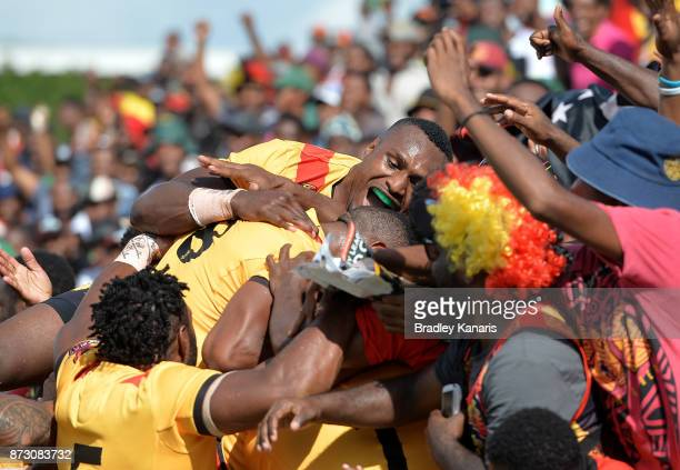 Lachlan Lam of Papua New Guinea is congratulated by team mates after scoring a try during the 2017 Rugby League World Cup match between Papua New...