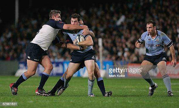 Lachlan MacKay of the Waratahs is hit high in a tackle as team mate Nathan Grey watches on during the Super 12 semi final match between the New South...