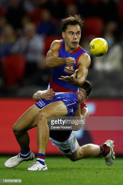 Lachlan McNeil of the Bulldogs handpasses the ball under pressure during the AFL Community Series match between the Western Bulldogs and the...