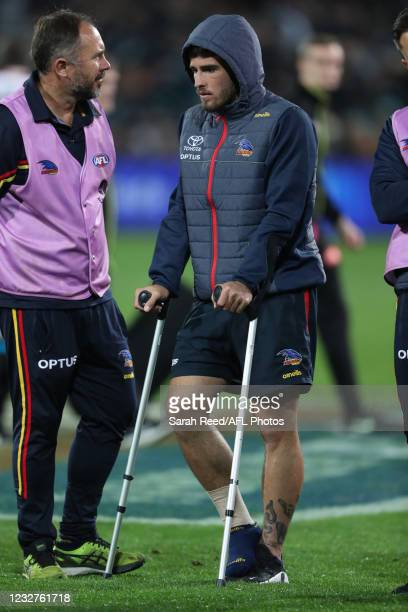 Lachlan Murphy of the Crows stands with the help of crutches after a serious ankle injury at the 3 quarter time huddle during the 2021 AFL Round 08...