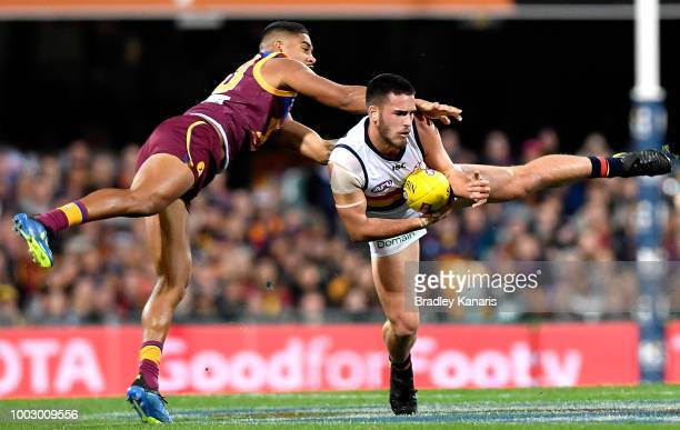 Oscar McInerney of the Lions is pressured by the defence during the round 18 AFL match between the Brisbane Lions and the Adelaide Crows at The Gabba...