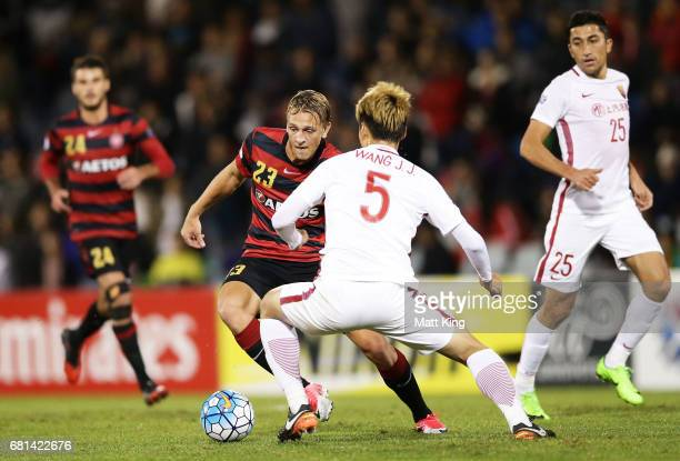 Lachlan Scott of the Wanderers is challenged by Wang Jiajie of Shanghai during the AFC Asian Champions League Group Stage match between the Western...