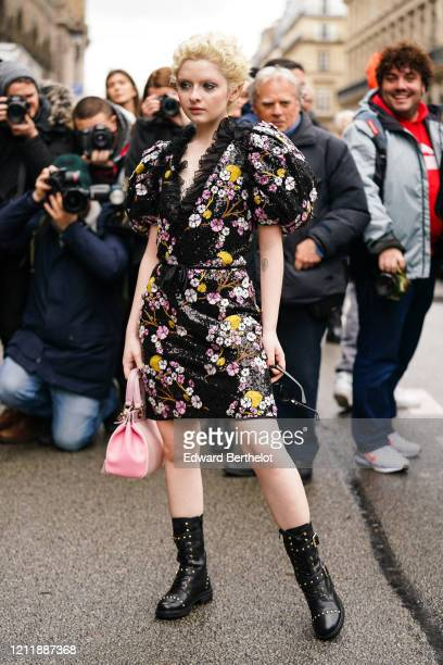 Lachlan Watson wears earrings a black dress with colorful floral embroideries puff sleeves and a plunging neckline with a black frilly collar a pink...