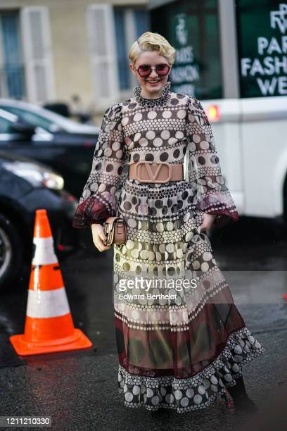 Lachlan Watson wears sunglasses a ruffled dress with printed patterns a large brown Valentino belt a bag outside Valentino during Paris Fashion Week...