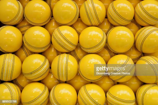 Lacquered yellow cricket balls await labeling
