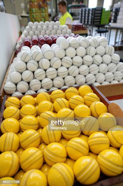Lacquered yellow white and red cricket balls sit in crates as they await labeling at the Kookaburra Sports Pty Ltd plant in Melbourne Australia on...