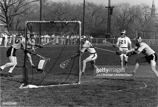 Lacrosse Action shot taken during an unidentified match Group of players surround the goal trying to prevent Hopkins player from making a goal 1950