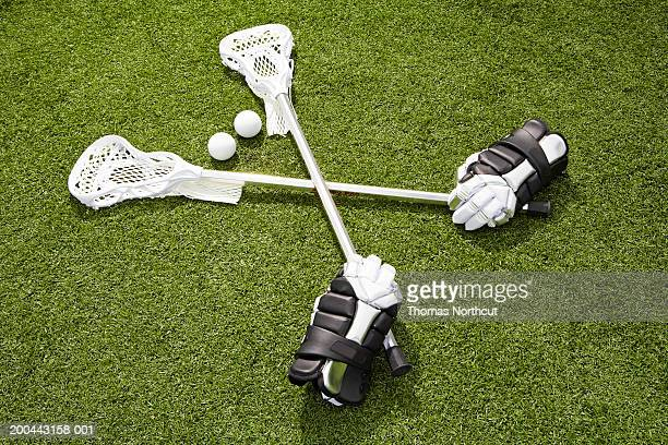 Lacrosse sticks, gloves and balls on artificial turf