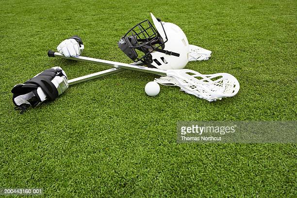 Lacrosse sticks, gloves, balls and sports helmet on artificial turf