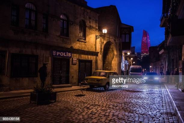 A Lada vehicle manufactured by AvtoVAZ OAO stands outside a police station as the Flame Towers stands in the background at night in the Old City of...