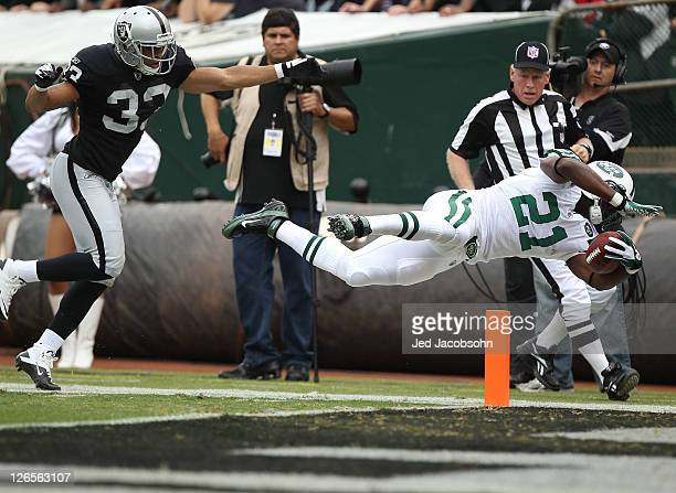 LaDainian Tomlinson of the New York Jets is pushed out of bounds at the one yard line by Tyvon Branch of the Oakland Raiders at Oco Coliseum on...