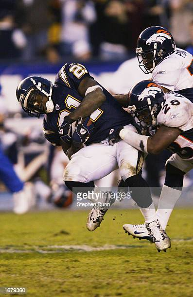 LaDainian Tomlinson of the San Diego Chargers is brought down after a gain in overtime by Kenoy Kennedy and Tyrone Poole of the Denver Broncos on...