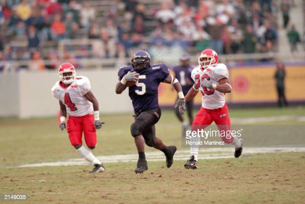 LaDainian Tomlinson of the Texas Christian University carries the ball as he is chased by Bryce McGill and Tierre Sans of Fresno State during a game...