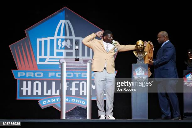 LaDainian Tomlinson reacts as he and presenter Lorenzo Neal unveil Tomlinson's bust during the Pro Football Hall of Fame Enshrinement Ceremony at Tom...