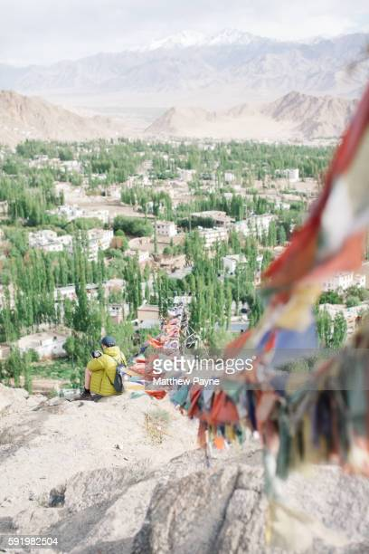 Ladakh, India: A hiker takes in view of Leh and Indus Valley with prayer flags