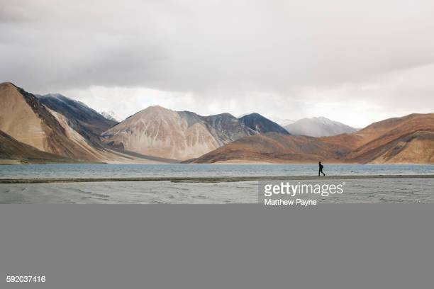 Ladakh, India: A hiker walks along the shore of Pangong Lake on the border between India and Tibet, in the Himalayas