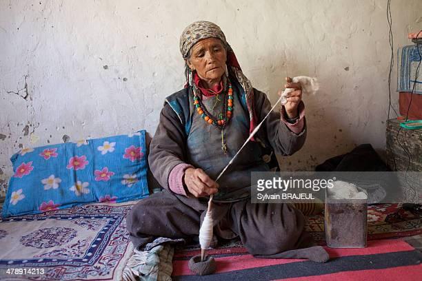 Ladakhi woman spin wool inside her house, Skyu, Markha Valley, Ladakh, India.