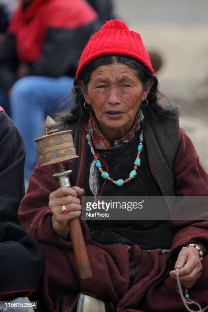 Ladakhi woman spins hand-held prayer wheels as she watches Buddhist monks perform ancient sacred dances during the Lamayuru Masked Dance Festival in...