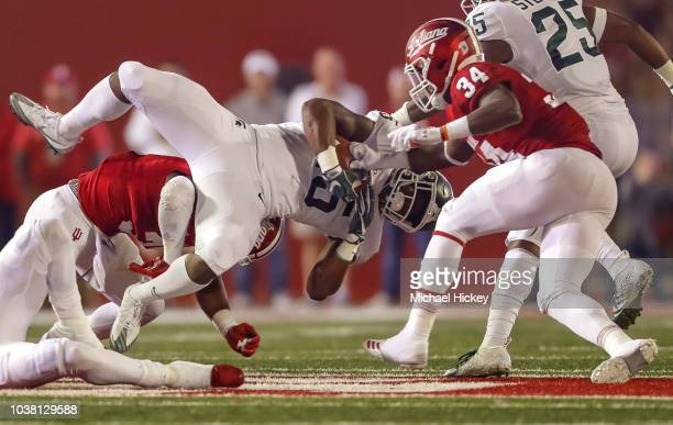 La'Darius Jefferson of the Michigan State Spartans runs the ball as Cam Jones of the Indiana Hoosiers punches the ball away causing a fumble during...