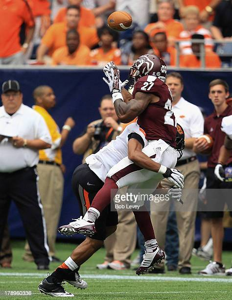 LaDarius Perkins of the Mississippi State Bulldogs can't hold on to the ball as he is hit by Lyndell Johnson of the Oklahoma State Cowboys during the...