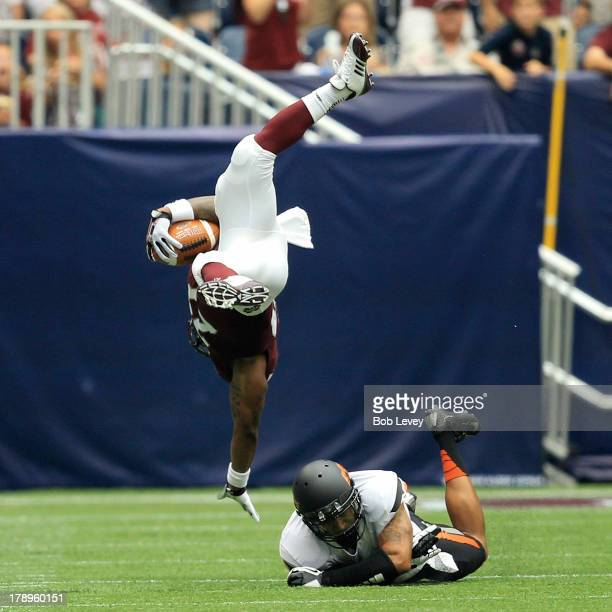 LaDarius Perkins of the Mississippi State Bulldogs is tripped up by Daytawion Lowe of Oklahoma State Cowboys at Reliant Stadium on August 31, 2013 in...