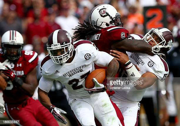 LaDarius Perkins of the Mississippi State Bulldogs runs with the ball as Jadeveon Clowney of the South Carolina Gamecocks hits Dak Prescott during...