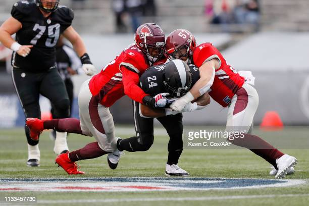 LadariusPerkins of the Birmingham Iron is tackled by ShaanWashington and JoelLanning of the San Antonio Commanders during the first half in an...