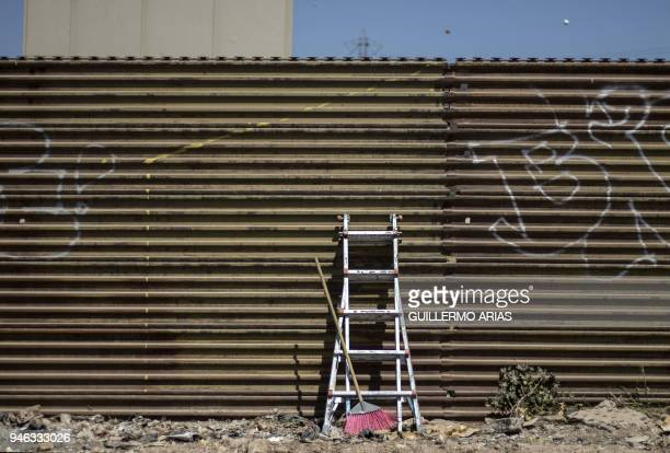 TOPSHOT A ladder and broom lean against the USMexico border wall as part of the Picnic prototype Security through Friendship activity at the border...