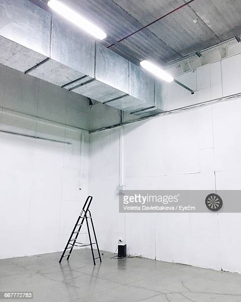 Ladder By Dartboard On Wall In Illuminated Building