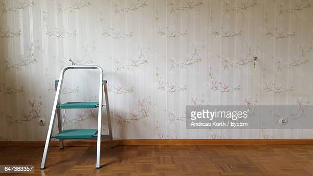 ladder in on hardwood floor next to wall - step ladder stock photos and pictures