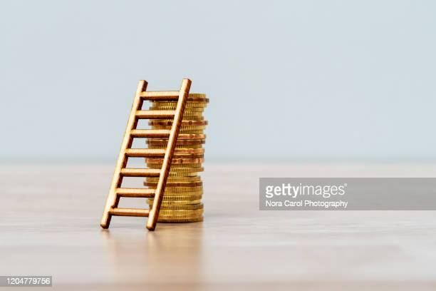ladder on stack of coins - capitalism stock pictures, royalty-free photos & images