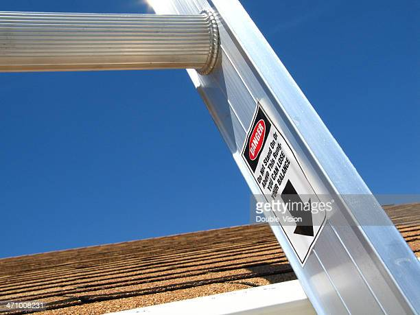 ladder safety: closeup of extension ladder, focusing on danger label - step ladder stock photos and pictures