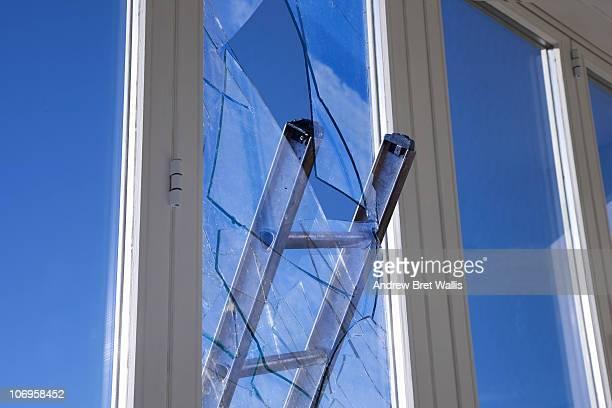 Ladder smashing through a glazed window pane