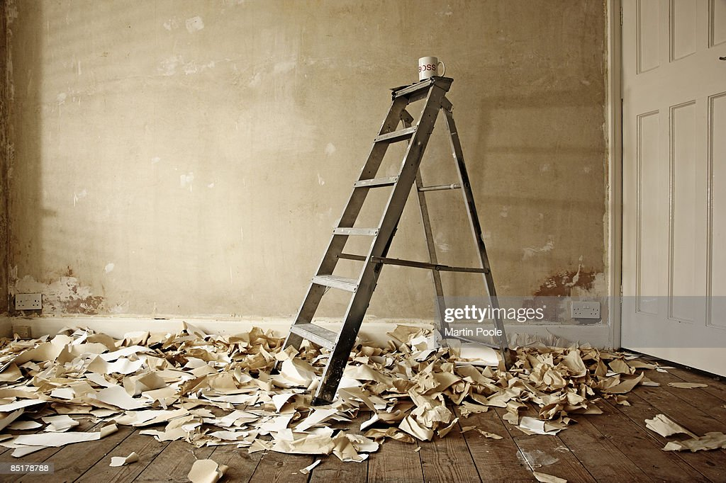 ladders next to a stripped bare wall : Stock Photo