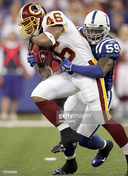 Ladell Betts of the Washington Redskins runs with the ball while Cato June of the Indianapolis Colts tackles him during the NFL game on October 22...