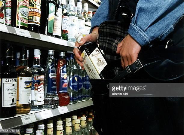 Ladendiebstahl in einem Supermarkt Frau packt heimlich eine Flasche Whisky in ihre Tasche 1997