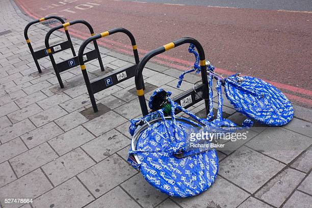 A ladies' bike covered in blue plastic wrapping tape is locked up on an empty bike stand in south London For unknown reasons this bike has been...